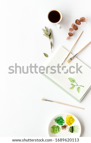 Painting herbs. Brushes and picture on white background top-down copy space