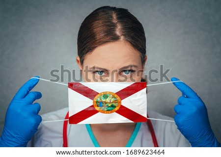 Coronavirus in U.S. State Florida, Female Doctor Portrait, protect Face surgical medical mask with Florida Flag. Illness, Virus Covid-19 in Florida #1689623464