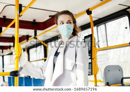 Woman wearing surgical protective mask pushing the button in a public transportation #1689657196