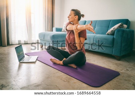 Attractive young woman doing yoga stretching yoga online at home. Self-isolation is beneficial, entertainment and education on the Internet. Healthy lifestyle concept. #1689664558