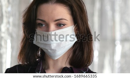 Sad woman with face mask looking to camera. Coronavirus, COVID-19 spread prevention concept. #1689665335