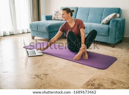 Attractive young woman doing yoga stretching yoga online at home. Self-isolation is beneficial, entertainment and education on the Internet. Healthy lifestyle concept. #1689673462
