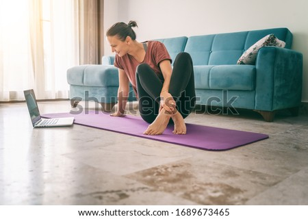 Attractive young woman doing yoga stretching yoga online at home. Self-isolation is beneficial, entertainment and education on the Internet. Healthy lifestyle concept. #1689673465