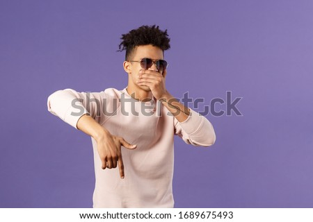Waist-up portrait of cool young handsome guy with dreads, sunglasses on, hold hand over mouth while beatboxing, waving hand to shake audience up, reading own rap, purple background #1689675493