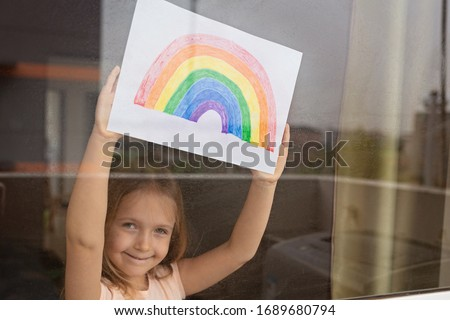 Kid painting rainbow during Covid-19 quarantine at home. Girl near window. Stay at home Social media campaign for coronavirus prevention, let's all be well, hope during coronavirus pandemic concept #1689680794