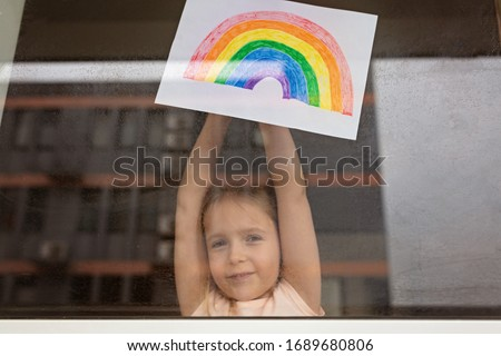 Kid painting rainbow during Covid-19 quarantine at home. Girl near window. Stay at home Social media campaign for coronavirus prevention, let's all be well, hope during coronavirus pandemic concept #1689680806