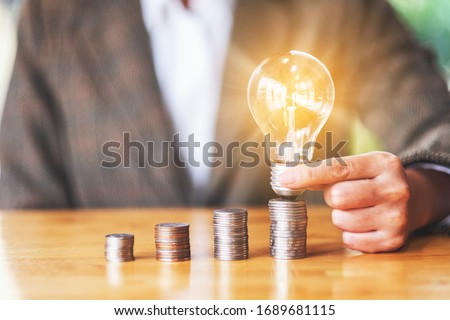 Businesswoman holding and putting light bulb on coins stack on table for saving energy and money concept Royalty-Free Stock Photo #1689681115