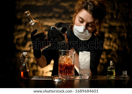 woman bartender in black clothes pours alcoholic into large glass with ice. White medical mask on her face and black gloves on hands for protection from coronavirus. #1689684601