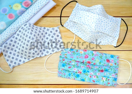 Top view Stack cotton and 3 type of DIY fabric cotton face mask on wood table. Protect saliva, cough, dust, pollution (PM2.5), Virus, Bacteria, COVID-19. Handmade. fashion concept. #1689714907