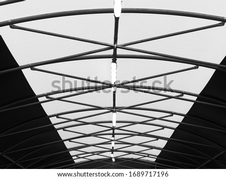 Low angle and perspective view of vaulted rood with steel pipe roof beams. Black and white abstract architecture image. #1689717196
