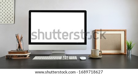 Photo of Computer monitor with white blank screen putting on working desk with wireless mouse, keyboard, pencil holder, stack of books, coffee cup and potted plant over white wall as background.