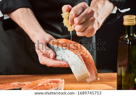 Man squeezing lime onto salmon steak, adding sour flavor to fish. Delicious gourmet seafood dish. #1689745753