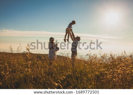 The concept of family and love. Parents with their son in summer field #1689772501
