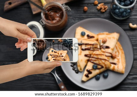 Food blogger taking picture of delicious thin pancakes at wooden table, closeup
