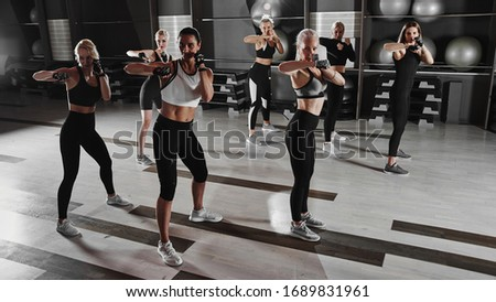 Women in black and white sportswear on a real group body Combat workout in the gym train to fight, kickboxing with a trainer Royalty-Free Stock Photo #1689831961