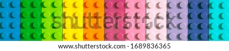 Many toy blocks in different colors making up one large square shape in top view. Toys and games. Royalty-Free Stock Photo #1689836365