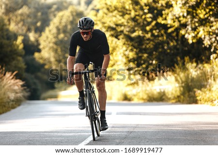 Full length portrait of active man in sport clothing and protective helmet riding bike with blur background of summer nature. Concept of workout and races. Royalty-Free Stock Photo #1689919477