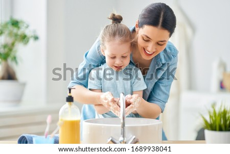 A cute little girl and her mother are washing their hands. Protection against infections and viruses. BAKU, AZERBAIJAN - MARCH 20, 2020 #1689938041