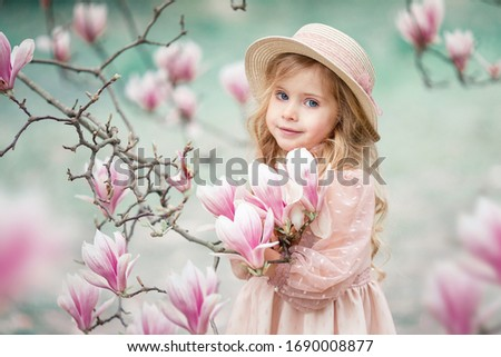 A little blonde girl in a pink dress and a straw hat near a Magnolia tree. Girl with blond hair in the Park