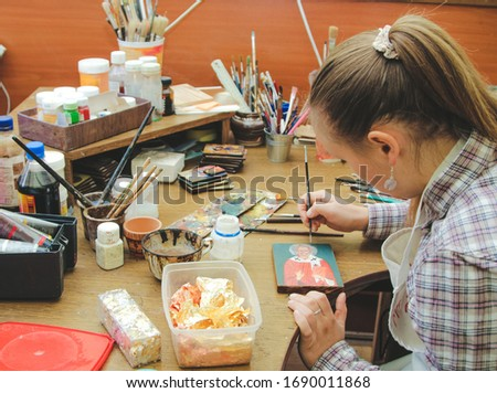 Girl artist paints a picture in the studio. Reproduction of the icon of St. Nicholas. Workflow of the artist in the studio. Brushes and paints on the background art workplace.