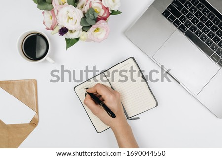 Top view of workspace desk with supplies and notebook, coffee, diary and stationery on white background, flat #1690044550