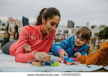 Woman playing with a small girl at the park. Girl child playing building blocks with her nanny at the park. Both lying on a plaid. Royalty-Free Stock Photo #1690046833