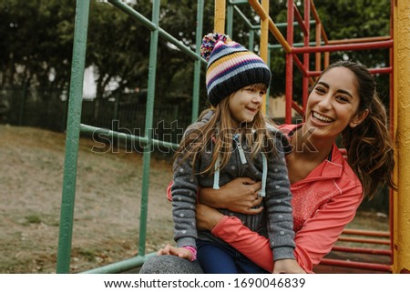 Woman spending time with a girl at the playground. Babysitter playing with a girl at the park. Royalty-Free Stock Photo #1690046839