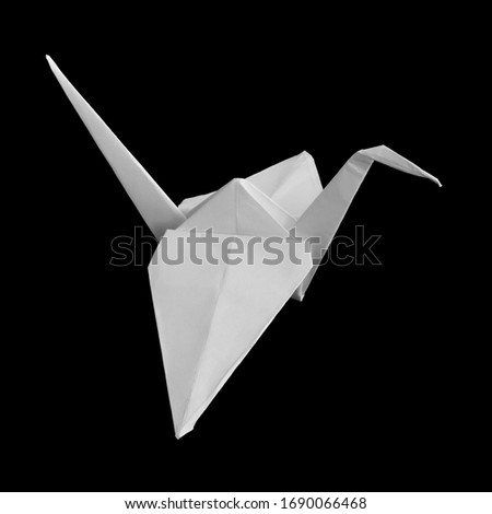 Handmade white origami paper crane (or orizuru) isolated on the black background. Symbol of peace, hope and happiness. Handicrafts theme. #1690066468