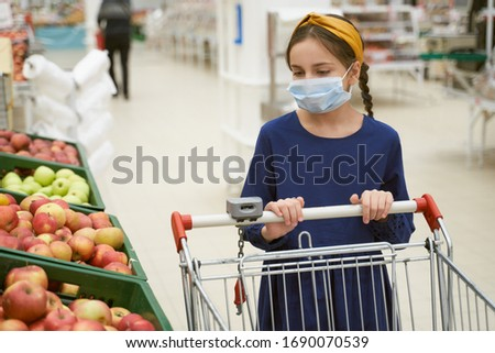 Girl in disposable medical mask shopping in supermarket during an outbreak of coronavirus pneumonia, makes panic stock of products. Empty store shelves, set of products for quarantine self-isolation #1690070539