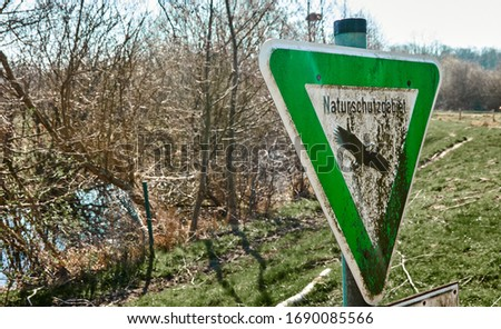 Green triangular sign with the picture of a bald eagle and the German inscription Nature reserve in front of a pond with a meadow and bushes