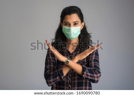 A portrait of woman with medical face mask showing stop sign with hands. Healthcare and medicine concept #1690090780