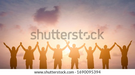 Silhouette of happy business teamwork making high hands over head in sunset sky background for business teamwork concept Royalty-Free Stock Photo #1690095394