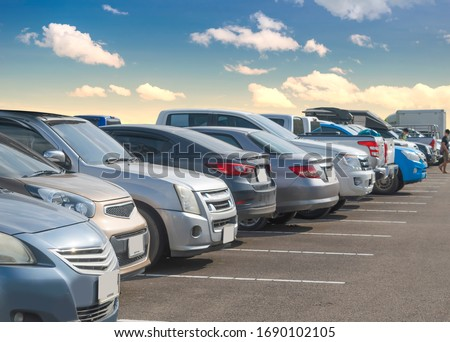 Car parking in large asphalt parking lot with white cloud and blue sky background. Outdoor parking lot with fresh ozone and green environment of transportation and modern technology concept #1690102105