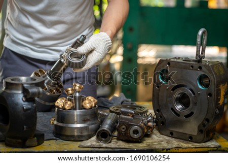 Professional mechanic man holding bearing of the hydraulic piston pump to inspection and repair maintenance heavy machinery  Royalty-Free Stock Photo #1690106254