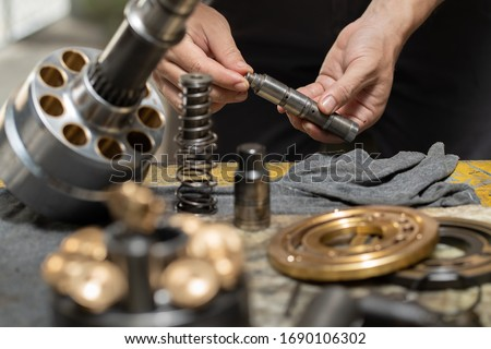 Professional mechanic man holding Valve rod of the hydraulic piston pump to inspection and repair maintenance heavy machinery  Royalty-Free Stock Photo #1690106302