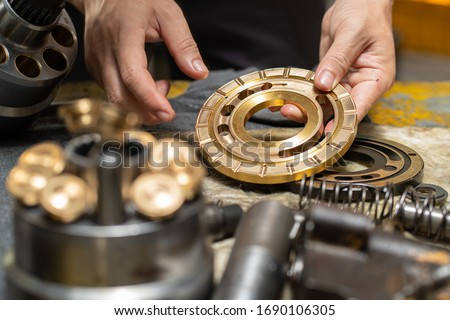 Professional mechanic man holding Valve plate of the hydraulic piston pump to inspection and repair maintenance heavy machinery  Royalty-Free Stock Photo #1690106305