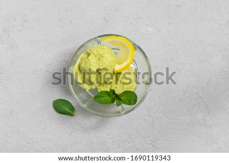 Homemade easy vegan dessert avocado ice cream with lemon and mint leaves in a glass bowl on grey background. Top view with copy space Royalty-Free Stock Photo #1690119343