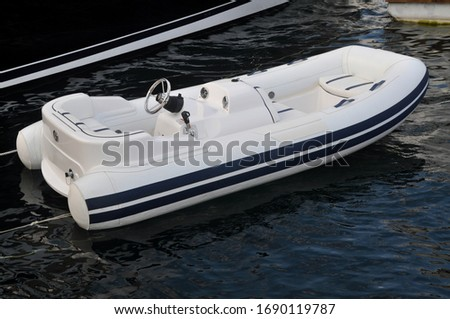 Modern inflatable boat with engine in the sea near shore, white inflatable boat #1690119787