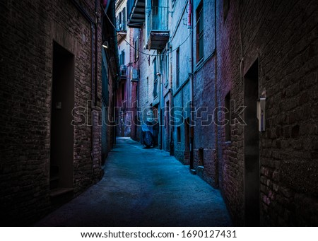 An atmospheric, narrow, back alley painted with blue and magenta light taken in Recanati, Macerata, Italy Royalty-Free Stock Photo #1690127431