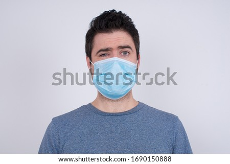 Handsome young man wearing face mask being nervous and scared about new disease afraid of being infected, looking camera with impatient expression, pensive. #1690150888