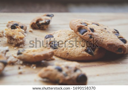 Close up picture of chocolate brown cookie with small chips on wooden brown background as snack for dinner with American taste of sweets, as homemade cooking wallpaper with food concept