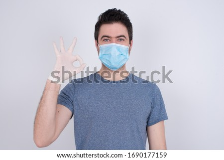 Glad attractive man shows ok sign with hand as expresses approval, has cheerful expression, being optimistic. Standing against gray wall. Protection against contagious disease. #1690177159