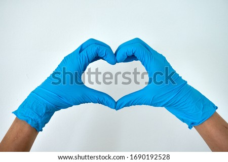 Human rising hands make finger heart shape wearing blue disposable latex glove, rubber glove for professional medical safety and hygiene protection from Coronavirus disease COVID-19 and surgery