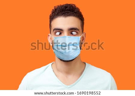 Portrait of comic crazy positive brunette man with surgical medical mask looking cross-eyed, having fun with silly face expression, playing fool. indoor studio shot isolated on orange background #1690198552