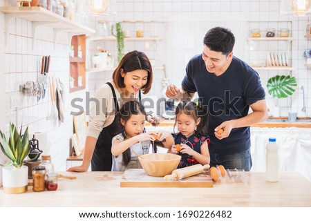Asian family enjoy playing and cooking food in kitchen at home #1690226482