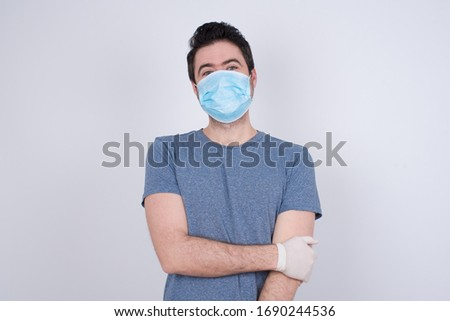 Lovely good-natured young caucasian man having charming smile and friendly expression holding himself wanting to show his love and sympathy. My heart is for you! Protection against contagious disease. #1690244536