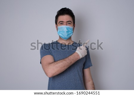 Look over there! Handsome blond caucasian man pointing away and smiling to you while standing against grey background. Protection against contagious disease. #1690244551