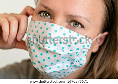 Portrait of woman wearing handmade cotton fabric face mask. Protection against saliva, cough, dust, pollution, virus, bacteria, COVID-19.  #1690275571
