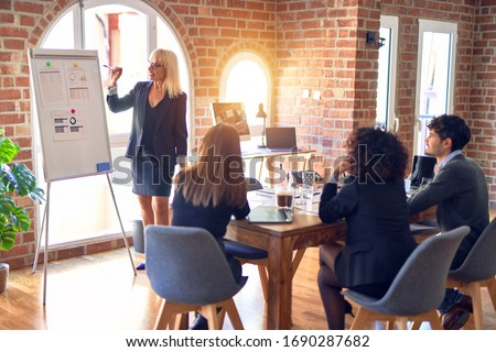 Group of business workers working together in a meeting. One of them making presentation to colleagues at the office #1690287682