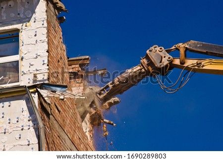 A demolition of a building with a crane with a blue sky background Royalty-Free Stock Photo #1690289803